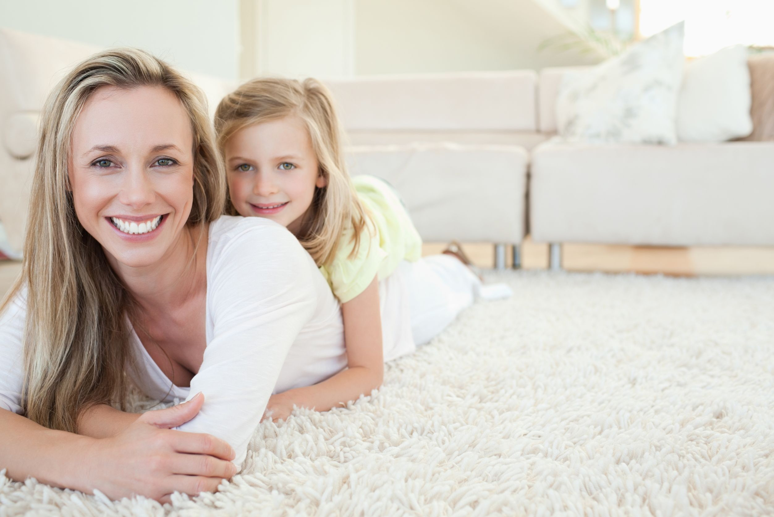 woman and daughter laying on clean carpet